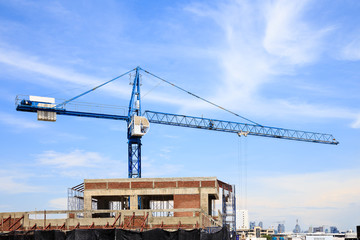 Blue tower crane at construction site with blue sky