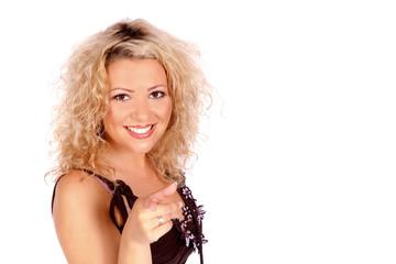Lächelnde junge Frau zeigt mit dem Finger nach vorne