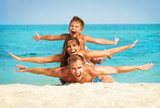 Happy Young Family with Little Kid Having Fun at the Beach