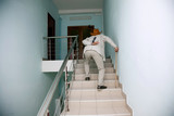 man climbs the stairs with the pain in his back