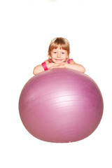 Happy little girl with fitness ball. Isolated on white