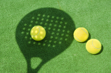 Paddle tennis racket shadow on ball.