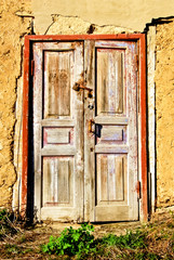 """The old,wooden front door with a padlock"""
