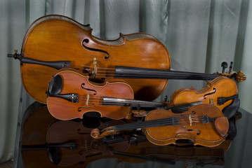 Two Violins, Viola and Cello on Piano on Curtain Background