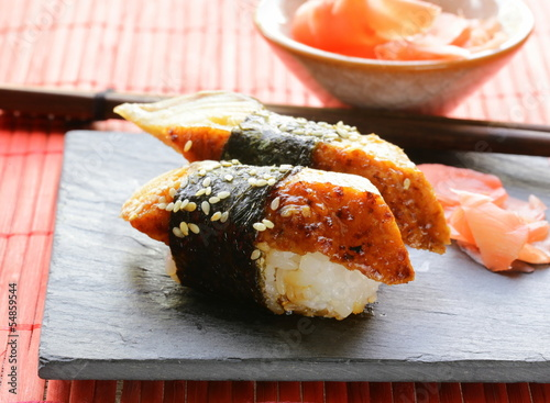 portion of sushi with smoked eel on a stone plate