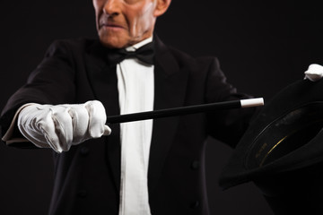 Magician with black suit and hat holding a magic stick. Studio s
