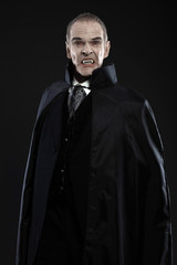 Dracula with black cape showing his scary teeth. Vamp fangs. Stu