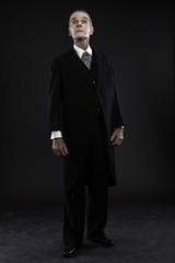 Scary count dracula in black suit. Pale head. Studio shot agains