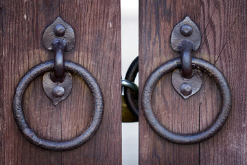 Ancient wooden gate with two door knocker rings close-up shot