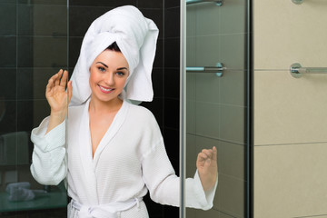 Young woman in bathrobe in hotel bathroom