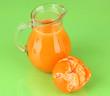 Full jug of tangerine juice, on wooden color  background