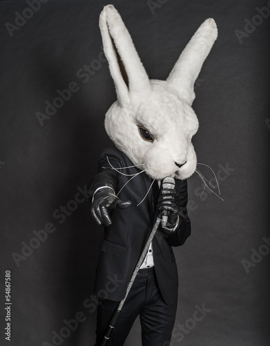 man in rabbit mask . black suit sing on dark background