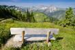 canvas print picture - Bank mit Ausblick auf eine Alm und Berge