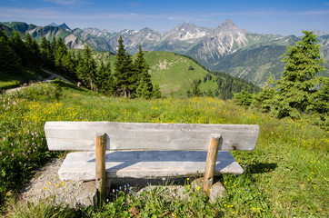 Bank mit Ausblick auf eine Alm und Berge