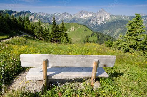 canvas print picture Bank mit Ausblick auf eine Alm und Berge