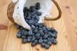 auf Holztisch liegende Blaubeeren mit Körbchen
