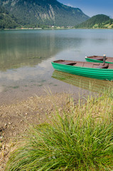 See in den Tiroler Bergen mit grünem Boot aus Holz