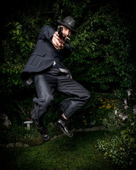 Man with Gun in Retro Suit Jumping