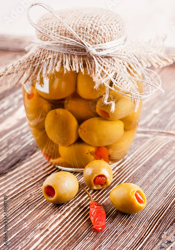 Bank of olives with pepper on a wooden board