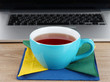 Blue cup on napkin on laptop background on wooden table
