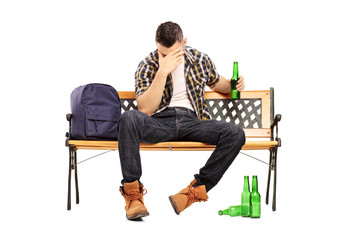 Drunk male teenager sitting on a bench and drinking beer