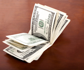 Folded 100 US$  Bills Stack on Brown Background
