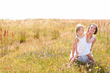 Junge Mutter mit ihrer kleinen Tochter auf Sommerwiese