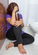 Drunk woman sitting on the toilet floor with a liquor bottle