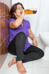 Latin woman lying drunk in the bathroom and drinking