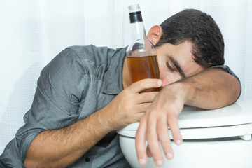 Drunk man sleeping on the toilet and holding a bottle