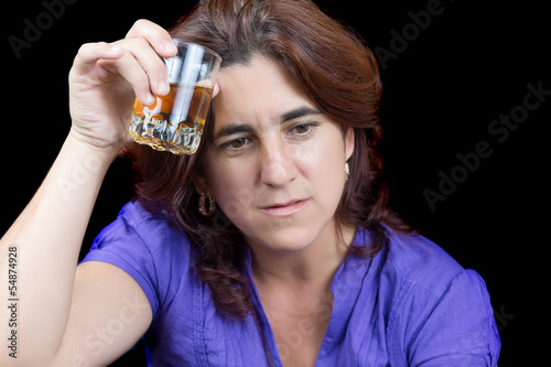 Drunk and sad latin woman holding a glass of liquor