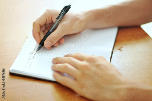 student hand with a pen writing on notebook