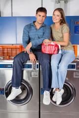 Couple Sitting On Washing Machines