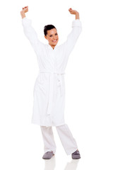 young woman in pajamas stretching arms