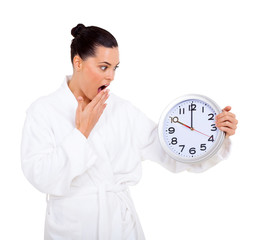 woman in bathrobe looking at the clock