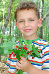 in the forest, a boy holding a bunch of strawberries.