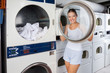 Woman Looking Through Washing Machine Lid