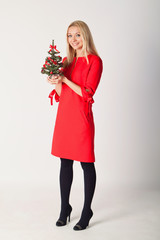 Beautiful blonde in a red dress holding a Christmas tree