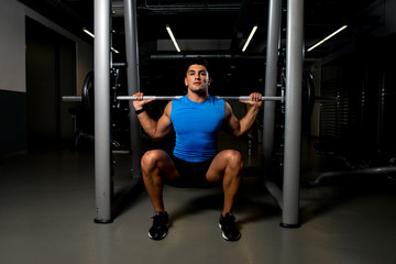 Young man exercising with barbell Squats