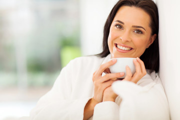smiling woman drinking coffee on bed
