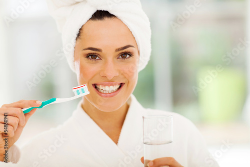 young woman with a smile brushing teeth