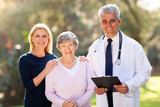 medical doctor standing with senior patient and her daughter
