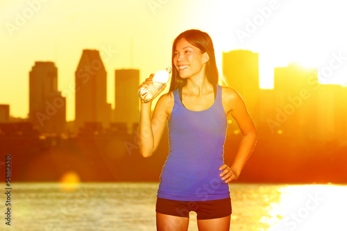 Fitness runner drinking water after city running