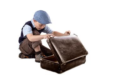 kleiner Junge schaut überrascht in einen Koffer