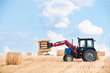 Tractor collecting round bales of straw.