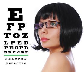brunette wearing glasses and Snellen eye exam chart isolated