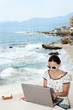 .A woman sends a message on your laptop in a seaside cafe