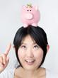 lächelnde Frau mit Sparschwein auf dem Kopf