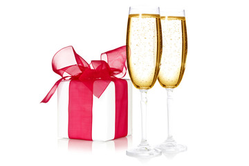 Glasses of champagne and a gift box