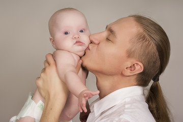 the father embraces the newborn child and smiles